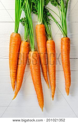 Fresh clean carrots on a white wooden table. Background of fresh vegetables top view. Fresh bunch of carrots on white background.