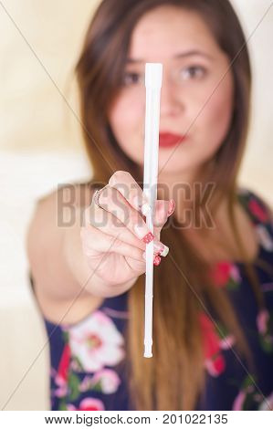 Close up of a young woman holding in her hands a medical object used for vaginal infection medicine, pointing in front of her face, in a blurred background.