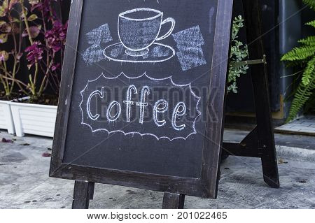 Hand written coffee message against chalkboard concept inscription in a rustic coffee shop.
