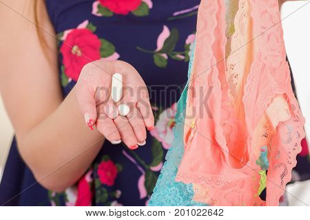 Close up of a woman hands, holding an assorted colorful underwears and a soft gelatin vaginal tablet or suppository, treatment of diseases of the reproductive organs of women and prevention of women's health.