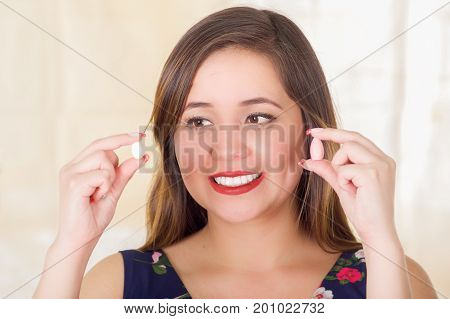 Portrait of a smiling woman holding in both hands a soft gelatin vaginal tablet or suppository, treatment of diseases of the reproductive organs of women and prevention of women's health, in a blurred background.