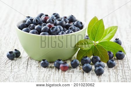 Blueberry with leaves on a wooden white board