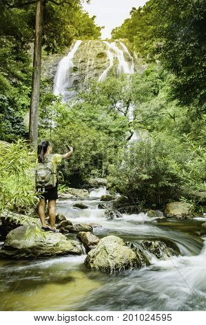 Travel and freedom. Young woman in selfie with backpack enjoying tropical waterfall view.