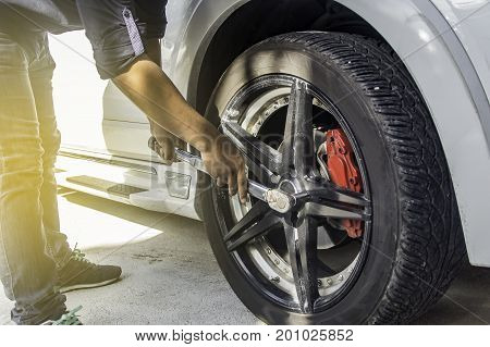Auto mechanic uses a Car changing tire in professional car repair service in the Auto Service Garage. Selective focus.