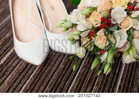 Wedding accessories: shoes and bride's bouquet on carpet
