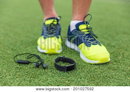 Fitness sport wearable devices man wearing running shoes with wireless earbuds, smartwatch lying on grass floor. Tech run gear, smart watch and earphones for runners.