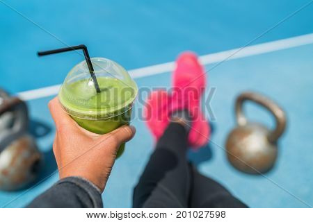 Fitness smoothie weight loss woman taking food selfie of detox green juice with kettlebells at outdoor training gym. Hand holding plastic cup of vegetable cleanse with kettlebell weights.