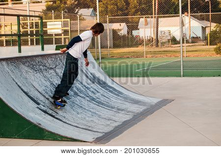 Active teenager riding a rip-stick at the skateboard park.