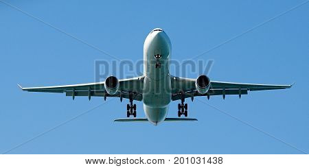 Commercial Jet Aircraft in a vibrant sunny blue sky head-on overhead on landing approach at Sir Kingsford Smith Airport Mascot Sydney Australia.