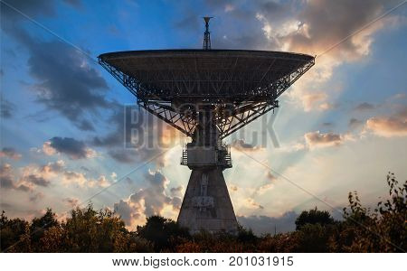 Silhouette of an old huge radio telescope to ensure the launch of spacecraft to the moon against the backdrop of the rays of the setting sun