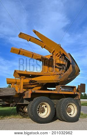 The huge  mounted  spade, jaws, and bucket are part of a tree removal machine used to dig out and transplant the tree, and root system.