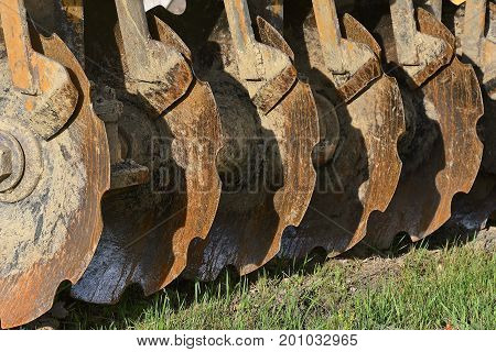 Row of Plain Cone Notched Disc Blades used in a field or construction site to break up the earth