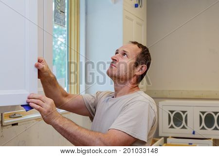 Worker Installing Kitchen Cupboard