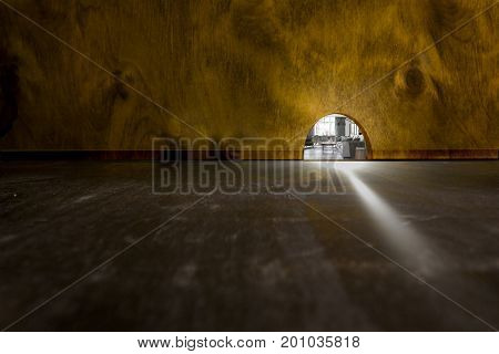 Mouse house that is visible through a hole in a wooden wall