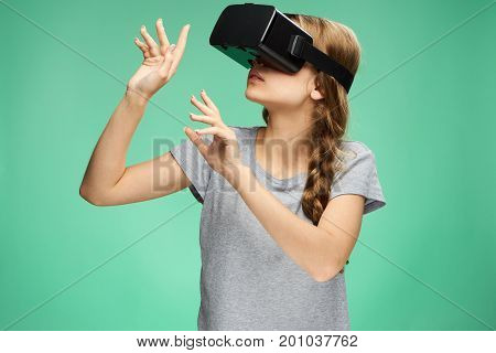 Young woman on a Green background with virtual reality glasses.