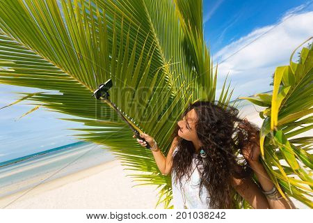 beautiful young woman taking selfie with selfie stick on the beach