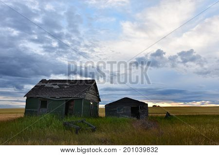 An image of an old abandoned homestead on the prairies.