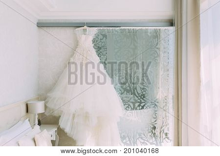 A Cream, Luxury Bridal Dress Which Hangs On The Cornice On A Background The Beige Ornate Wall.