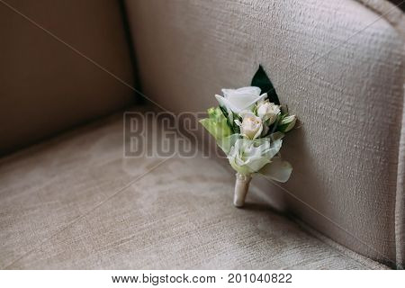 White Boutonniere From Roses Lie On Armchair