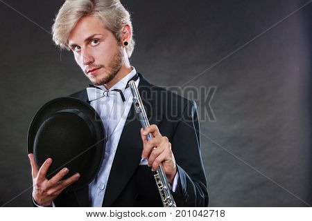 Classical music passion hobby concept. Elegantly dressed musician man holding flute and black fedora hat. Studio shot on dark background