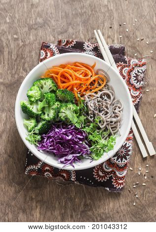 Broccoli buckwheat noodles red cabbage and pickled carrots buddha bowl on wooden background top view. Vegetarian healthy diet food concept
