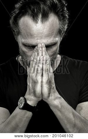 Monochrome portrait of upset man showing emotion of deep sorrow. Close up view of man holding both hands on his face.