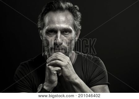 Low key portait of mature depressed man. Beardy male looking in camera isolated on black backdrop.