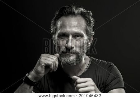 Black and white portrait of self confident brutal man. Mid aged male showing fists on black background.