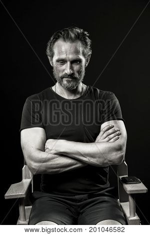 Monochrome portrait of stong man sitting on chair in studio. Male with crossed hands sitting looking down.