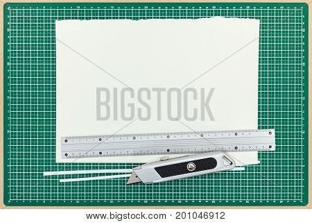 Paper Sheet With Metal Ruler And Utility Knife On Green Cutting Mat