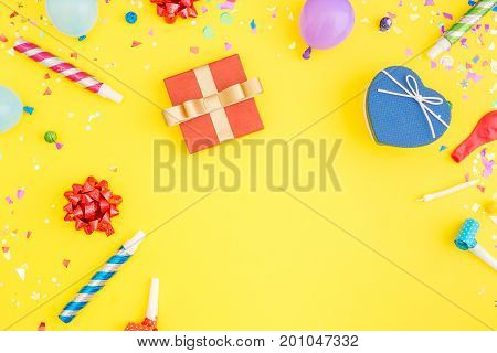 Colorful celebration pattern with various party confetti balloons gift box on yellow background. Flat lay