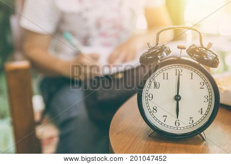 Time For Working Concept. Clock Timed At 8 O'clock With Blur Working People Background.