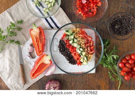 Black quinoa chickpeas peppers cucumber tomatoes and parsley on wooden table top view. Summer Vegetarian Salad with Ingredients for cooking vegetarian healthy salad