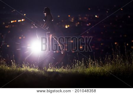Close-up of a loving couple dancing against a background of the night sky with stars in the background a night city - bokeh blurred. Concept first love kiss dance at night love without boundaries. copyspase