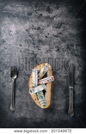 Crust Of Bread Full Of Dollar Banknotes Fork And Knife On Concrete Board. Toned Image