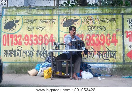 Dhaka, bangladesh, august 2017- a man sewing and tailoring at street footh path against wall located at motijhil in dhaka in bangladesh taken on 14, august 2017