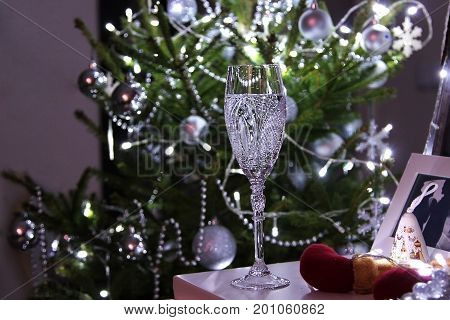 Concept of lonely on Christmas night. A glass of champagne against lighiting Christmas tree.