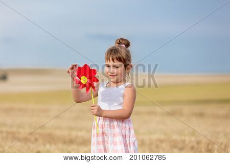 Little Girl In Classic Dress Holding Pinwheel Toy