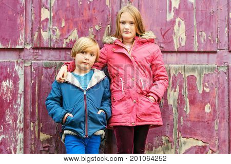 Portrait of two adorable kids outdoors wearing warm coats standing next to old purple background