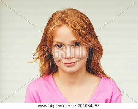 Outdoor portrait of cute little 8-9 year old girl with long red hair wearing pink jacket standing against white background