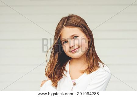 Outdoor portrait of cute little 8-9 year old girl with brown hair wearing white jacket standing against white background
