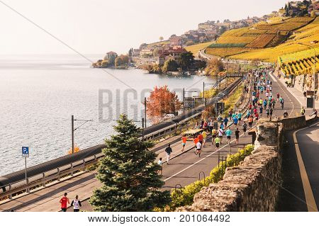 Lausanne area Canton of Vaud Switzerland- October 30 2016: Runners in the Lausanne Marathon going through Lavaux vineyards on swiss frech riviera