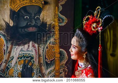 Chachoengsao Thailand - July 14 2013 : Beautiful woman with traditional chinese red dress at Chinese shrine door with painting of ancient soldier in Thailand.