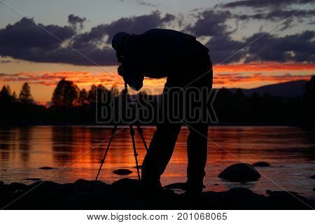 Silhouette of photographer framing a shot taking pictures on the river at sunset