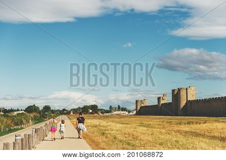 Family enjoying promenade around famous fortification wall surrounding Aigues-Mortes city Camargue France