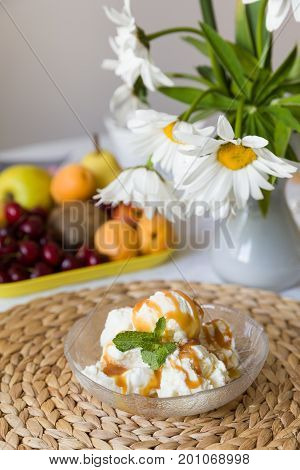 Homemade frozen yogurt or ice cream served with caramel. Delicious sweet dessert on the table with fruit background