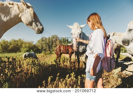 Girl tourist enjoying a trip to South of France white wild horse in Parc Regional de Camargue - Provence.
