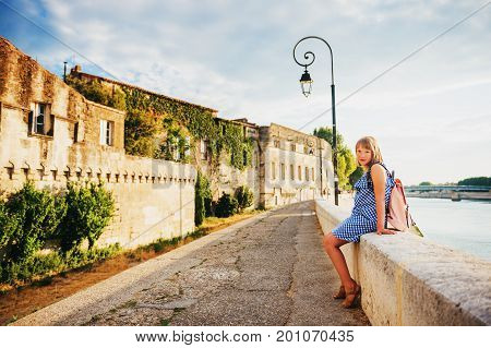 Kid girl tourist resting on quay of Arles Provence south of France wearing blue gingham dress and pink backpack. Travel with children