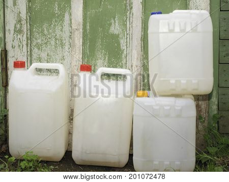 Platic canisters with water or other liquid next to the wooden barn wall