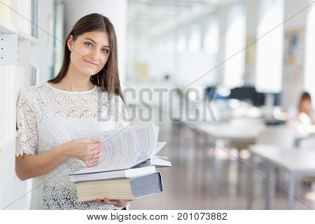 Pretty, young college student looking for a book in the library, studying for her exam